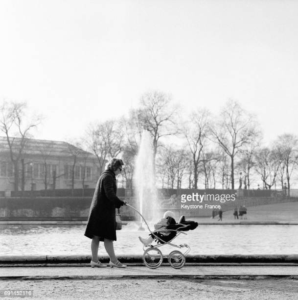 Une maman promène son enfant en poussette dans le Jardin des Tuileries à Paris France le 16 janvier 1968