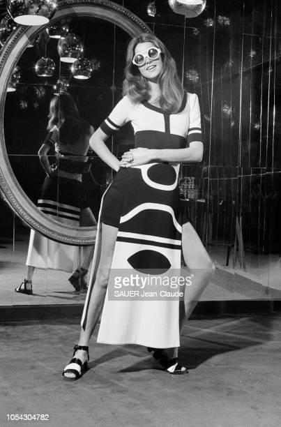 Une mannequin en pied portant une tenue du couturier Louis FERAUD de la collection printempsété 1971 une robepagne en jersey noir et blanc sur un...