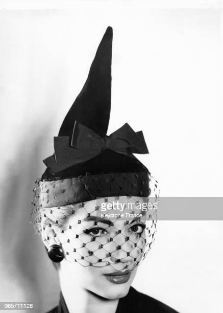 Une mannequin porte le chapeau 'Capricorn' avec une voilette créé par le couturier Digby Morton le 27 juillet 1955 au RoyaumeUni