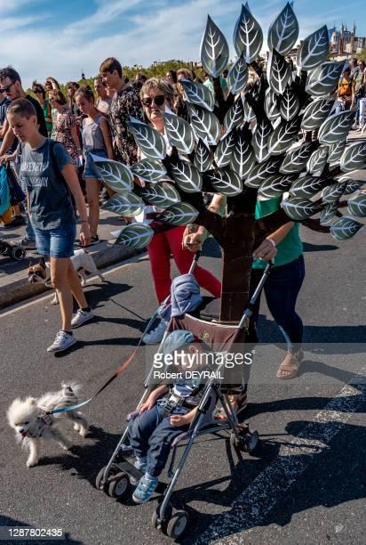 """Une mère avec une poussette où son enfant dort tient, un petit chien et une reproduction d'un arbre lors de la """"Marche pour le climat"""" réunissant..."""