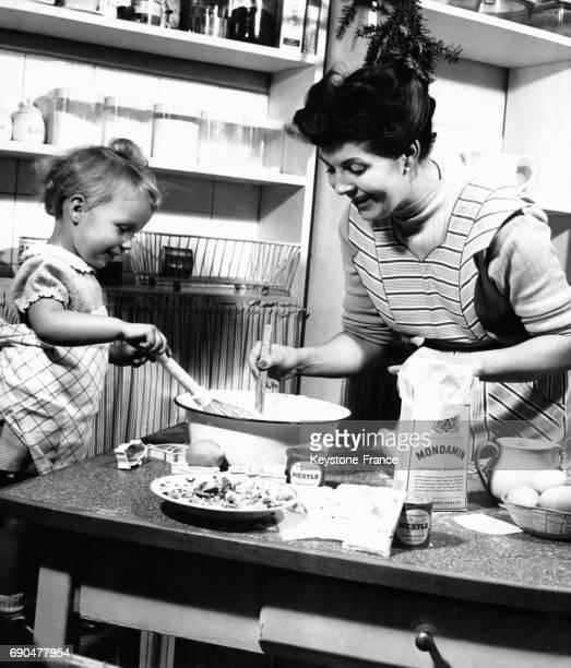 Une mère et sa toute jeune fille font de la pâtisserie dans la cuisine
