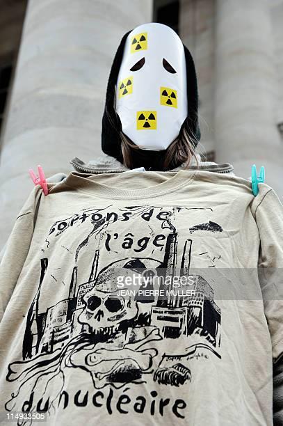 """Une personne affublée d'un masque et d'un t-shirt portant l'inscription """"Sortons de l'âge du nucléaire"""", manifeste sur la place de la comédie à..."""