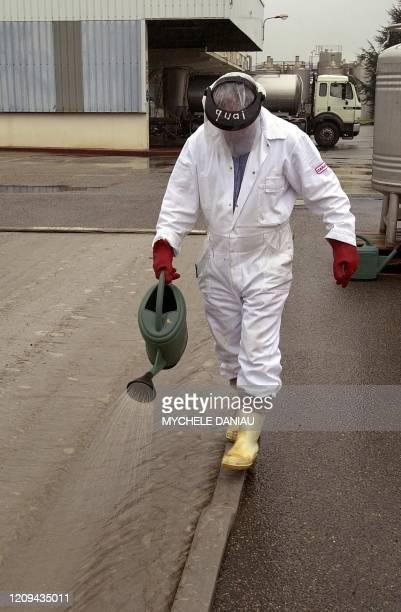 Une personne arrose d'eau et de soude caustique un rotoluve, le 15 mars 2001 à Beuvillers, mis en place au sein même de l'entreprise Nestlé, sur...