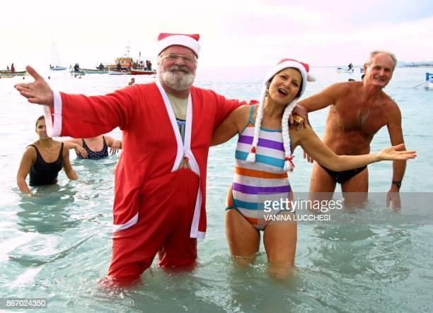 une personne déguisée en Père Noël se baigne aux côtés de participants le 15 décembre 2002 à Nice lors du traditionnel bain de Noël A man disguised...
