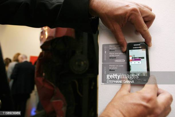 Une personne effectue une démonstration de l'application 'Découverte d'une uvre d'art' au moyen d'un téléphone au Musée d'Art Moderne et d'Art...