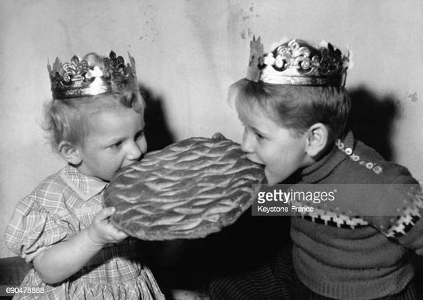 Une petite fille et son frère chacun coiffés d'une couronne des Rois croque un morceau de la galette lors de l'Epiphanie le 3 janvier 1958 en France