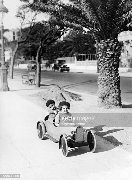 Une petite fille et un petit garçon dans une petite voiture sur un trottoir de la promenade des Anglais le 20 décembre 1929 à Nice, France.