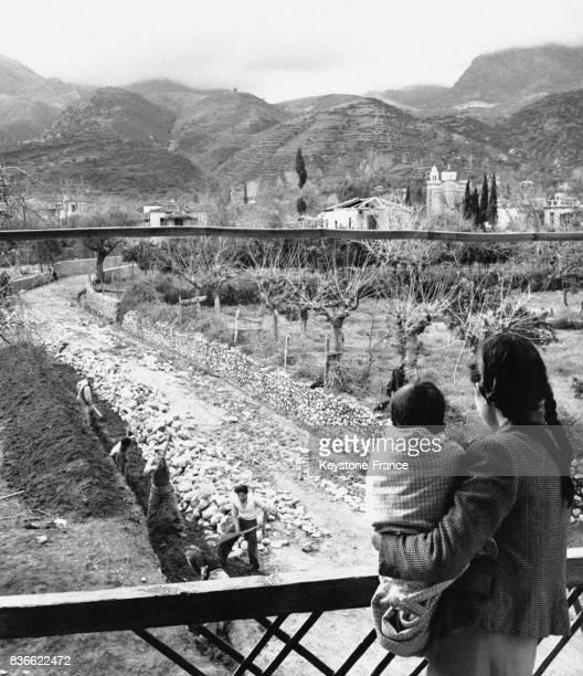 Une petite fille grecque sa jeune soeur dans les bras regarde depuis le balcon de sa maison son père participer à la construction d'une route reliant...
