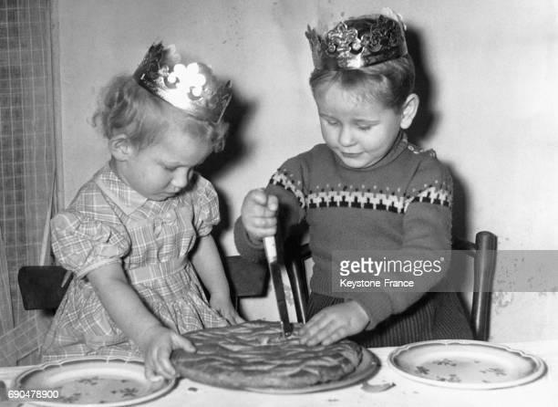 Une petite fille tient fermement la galette des Rois que son petit frère est en train de couper avec un couteau chacun portant la couronne par...