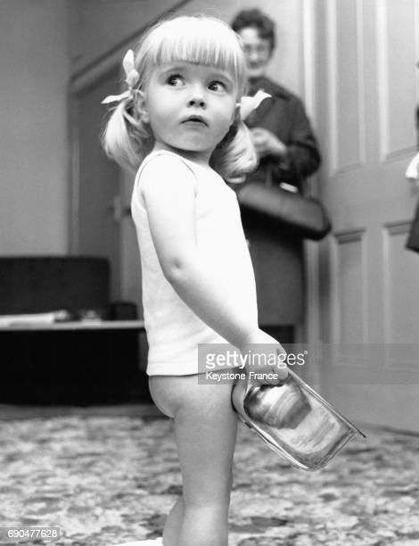 Une petite fille tient à la main son pot en or massif idée du créateur David Golley afin de contourner la loi britannique interdisant de conserver de...