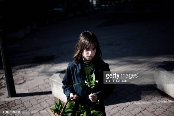 Une petite fille vend le traditionnel muguet « porte-bonheur », le 01 mai 2008 dans les rues de Lyon. Originaire du Japon, la plante aux fières...