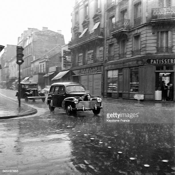 Une Peugeot 203 familiale roule sous les grêlons devant un passage clouté dans les rues de LevalloisPerret France le 9 juillet 1956
