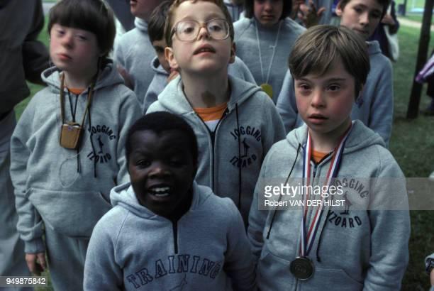 Une équipe d'enfants trisomiques porte autour du cou la médaille sportive qu'elle a remportée en juin 1981