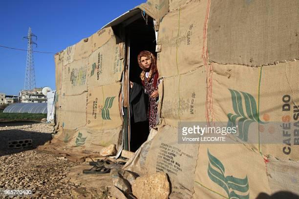 Une réfugiée syrienne se tient à l'entrée de sa tente réalisée à laide de vieux sacs en toile de jute cousus les uns aux autres dans un camp de...