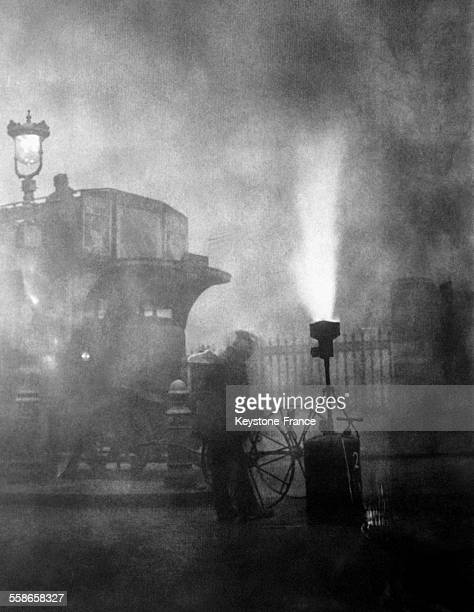 Une rue londonienne lors d'un brouillard dense en plein midi éclairée par une lampe à acétylène le 10 décembre 1930 à Londres RoyaumeUni