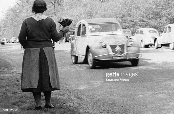Une vendeuse de muguet s'est postée au bord de la route afin de proposer des bouquets de muguet aux automobilistes le 1er mai 1957