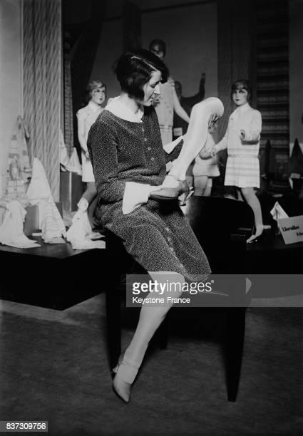 Une vendeuse tient la jambe avec une chaussure d'un mannequin dans une boutique qui semble être la sienne par une illusion d'optique du fait qu'elle...