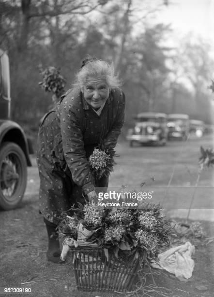 Une vieille femme vend du muguet dans les rues de Paris France le 1 mai 1934
