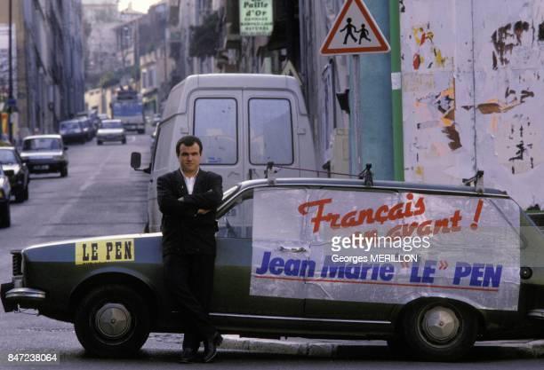 Une voiture aux couleurs du Font National de JeanMarie Le Pen et un militant dans une rue pendant la campagne presidentielle en avril 1988 a...