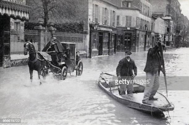 Une voiture à cheval et deux hommes sur une barque se fraient un chemin dans l'eau inondant les rues lors de la crue de la Seine en 1910 à Paris...
