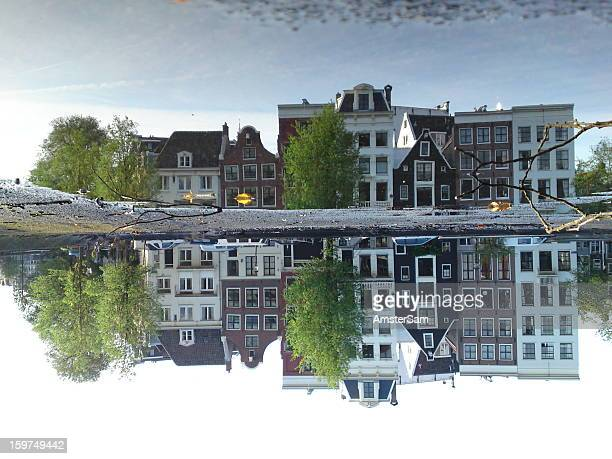 Unedited mobile phone cam photo of buildings reflected in a puddle on the roof of a house boat in Amsterdam. No editing, no tricks, no Photoshop.