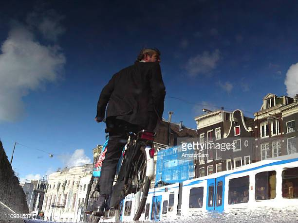 Unedited mobile phone cam shot of a biker a tram and buildings reflected in a puddle on the Rokin in Amsterdam