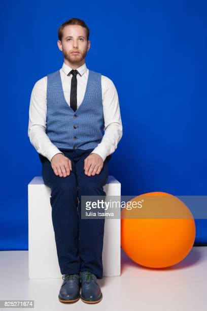 unemotional man on cube in studio - multi colored suit stock photos and pictures