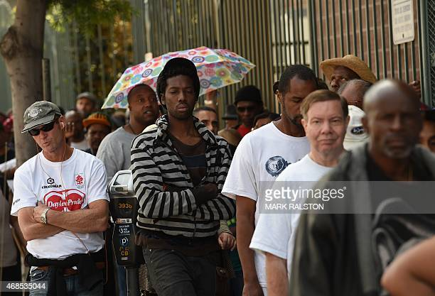 Unemployed and homeless people line up for a free meal and new shoes during a Good Friday event in Los Angeles California on April 3 2015 After a...