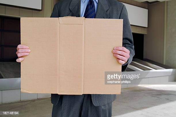 Unemployed Businessman Holding a Blank Cardboard Sign