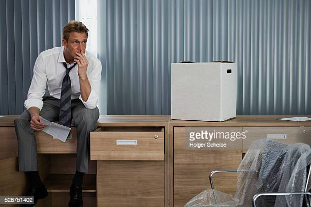 unemployed businessman packing in empty office - downsizing unemployment stock pictures, royalty-free photos & images