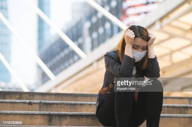 unemployed businesswoman depressed sitting on a path due to company bankrupted while coronavirus spreading situation - sin esperanza fotografías e imágenes de stock