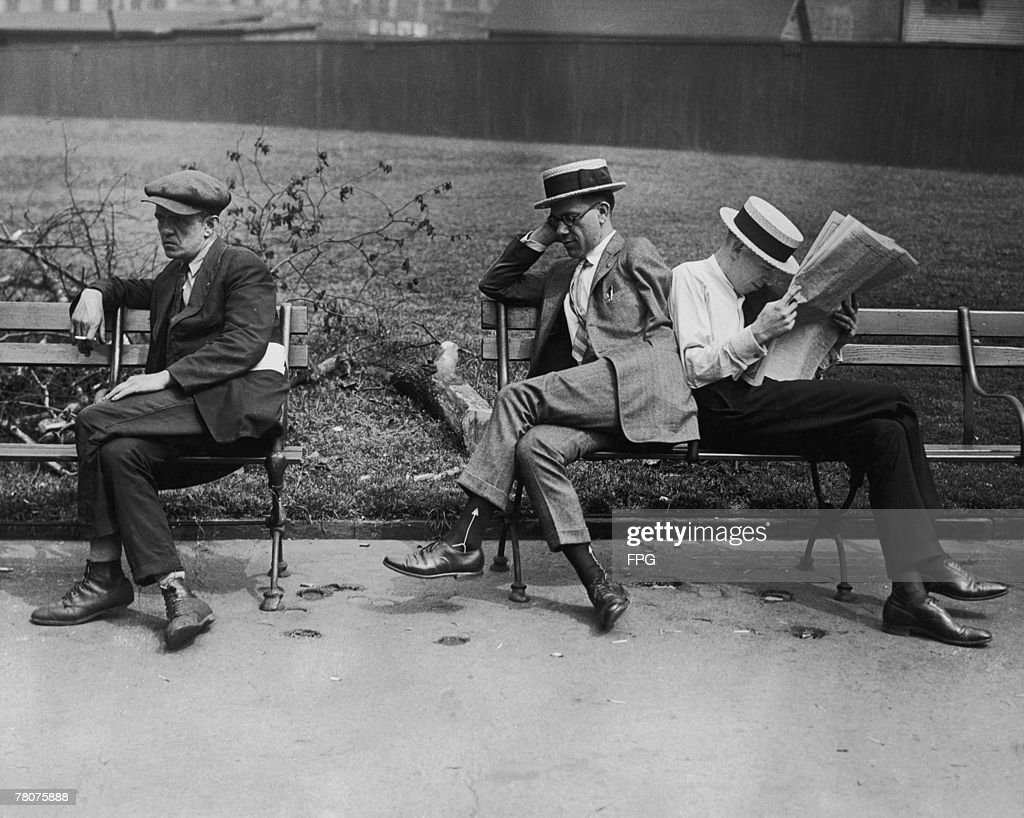 Unemployed First World War veterans, one of them disabled, sitting in a park, circa 1925.