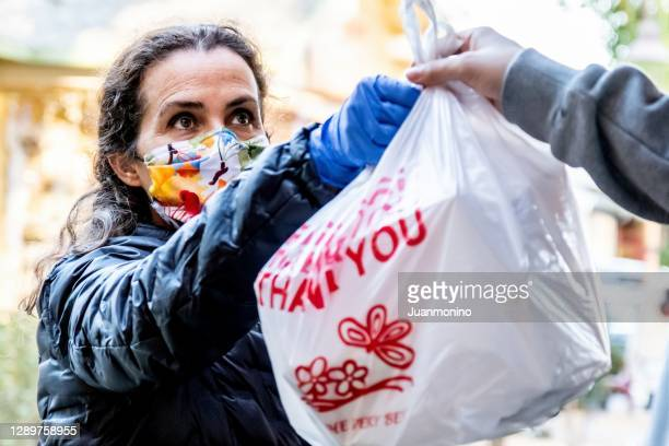 unemployed mature woman receiving free meal from charity center wearing a protective face mask - crisis stock pictures, royalty-free photos & images