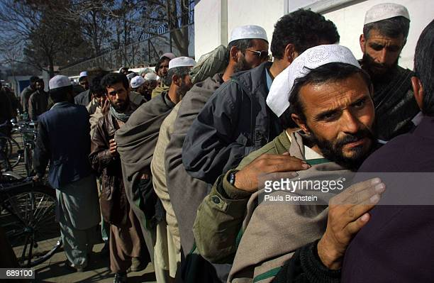 Unemployed men anxiously try to register their names in front of the United Nations office December 27 2001 in Kabul Afghanistan in order to get back...