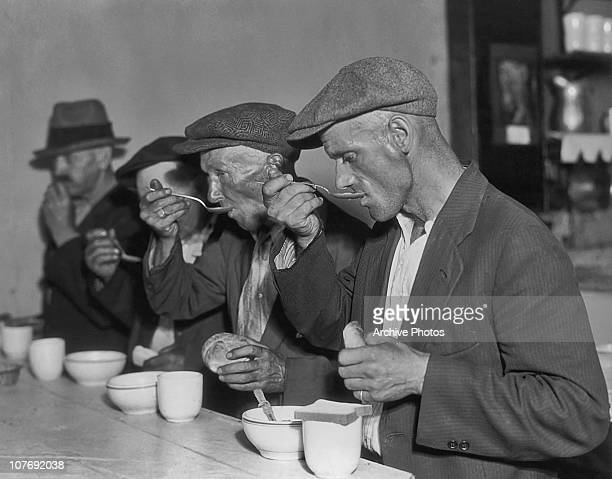 Unemployed men eating soup and bread at Bernarr Macfadden's Penny Cafeteria, probably in Washington DC, USA, circa 1935. Macfadden was a publisher...