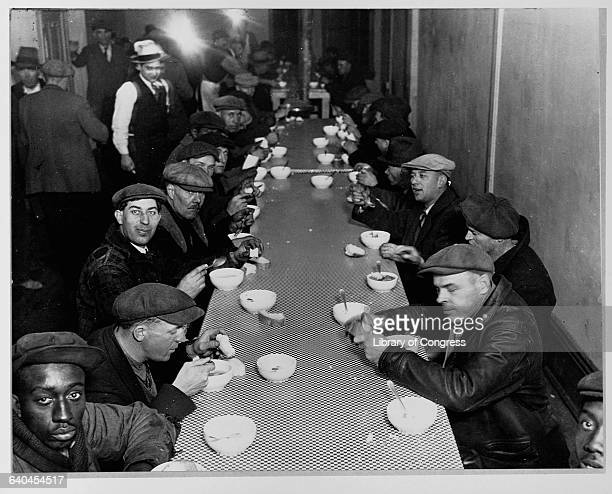 Unemployed men enjoy a meal at a soup kitchen financed by Al Capone on State Street in Chicago Illinois