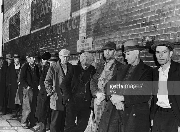Unemployed men queuing for food during the Great Depression, Iowa, USA, circa 1935.