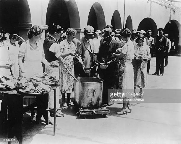 Unemployed men receiving soup and slices of bread in an outdoor breadline during the Great Depression, Los Angeles, California. Some women serve the...
