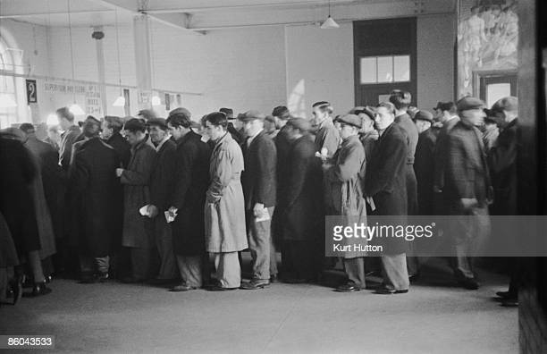 Unemployed men wait in line to draw their unemployment benefit at Peckham Labour Exchange south London January 1939 Original Publication Picture Post...