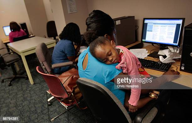 Unemployed mother Janet Francis looks for a job while her daughter Kayli sleeps on her shoulder at the New York State Labor Department's Division of...