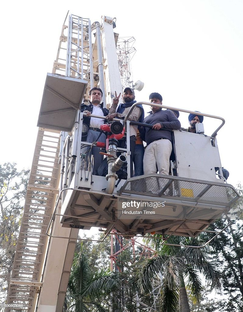 Unemployed teacher Deepak Kumar showing victory sign as he climbed down after receiving appointment letter from a mobile tower at Punjab Bhawan...