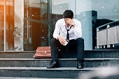 Unemployed Tired or stressed businessman sitting on the walkway after work Stressed businessman concept