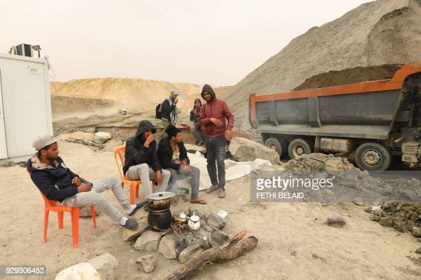 Unemployed Tunisians sit at a phosphate production plant in Kef Eddour in the Metlaoui mining region one of the main mining sites in central Tunisia...