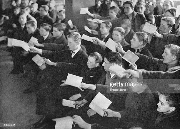 Unemployed unskilled workers holding up their identification cards to attract attention in the crowded offices of Berlin's unemployment agencies...
