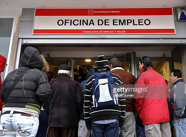Unemployed wait in line at a government employment office on February 5 2009 in Madrid Spain With companies shedding tens of thousands of jobs due to...