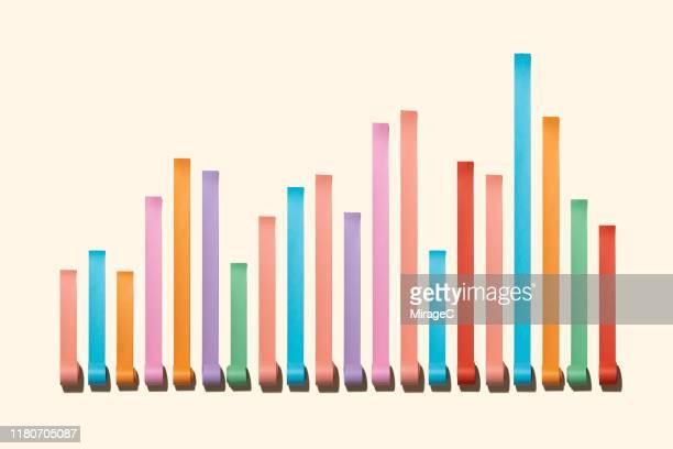 uneven chaos bar chart made of paper rolls - balkendiagramm stock-fotos und bilder