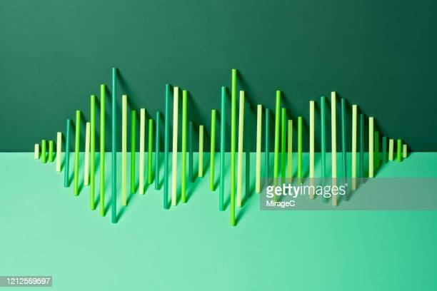 uneven green plastic pipes leaning on green - sound wave stock pictures, royalty-free photos & images