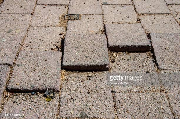 uneven paving stones present a trip hazard on a pedestrian walkway - pflasterstein stock-fotos und bilder