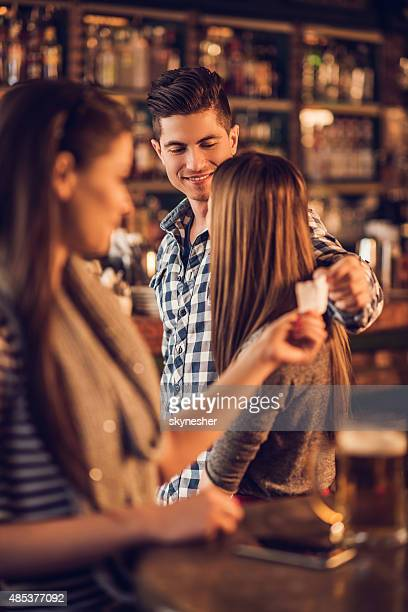 unfaithful man giving his phone number in a cafe. - bigamy stock pictures, royalty-free photos & images
