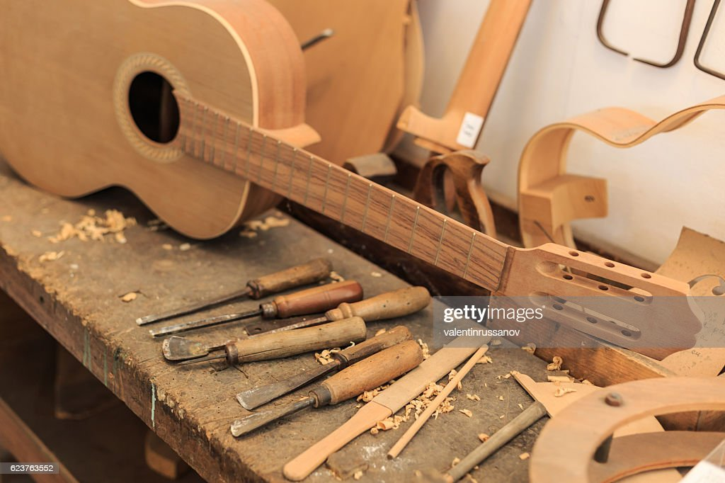 Unfinished acustic guitar and tools in workshop : Stock Photo